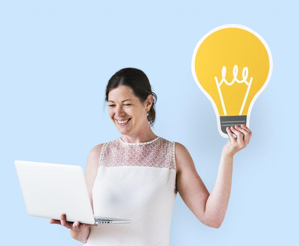 Mulher segurando um icone de ideia e usando um laptop para começar a empreender